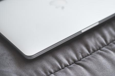 Closed Macbook Laptop on a Sofa